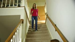 teenage girl walks down  stairs to meet her friends