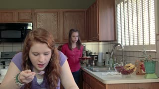 teenage girls eating and using a smart phone in the kitchen.