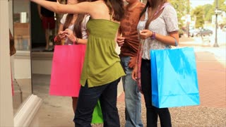 teenagers window shopping and smile at friend