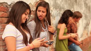 teens talking against an old wall