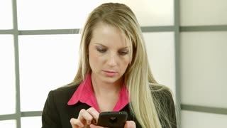 texting on smart phone brings smile from businesswoman.