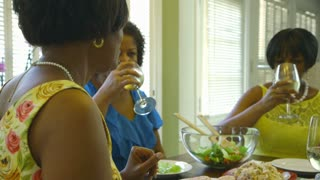 three women drinking wine and talking during lunch
