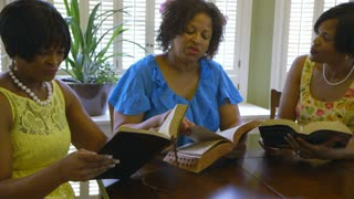 three women having daily bible study.