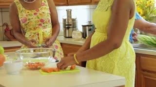 three women in a kitchen making a salad