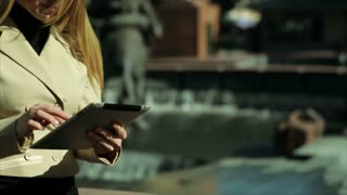 tilt businesswoman with tablet outside