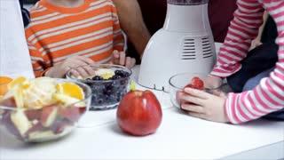 tilt down dad and kids pouring fruit in blender