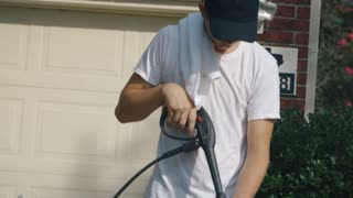 tilt teenager power washing driveway