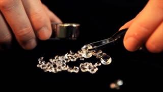 tilt up jeweler looking at diamonds