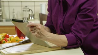 tilt up to mature woman using a tablet pc.