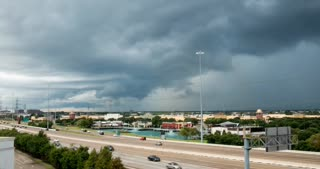 Time lapse footage of storm clouds and surrounding stormy weather in sky above travelers on section of hwy 59 in Stafford Texas