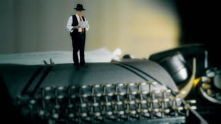 tiny film noir style man reading and pacing on vintage typewriter
