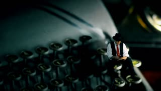 tiny film noir writer sitting on a vintage typewriter
