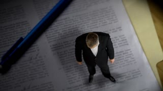 Tiny lawyer standing over contract paperwork