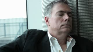 tired businessman sleeping in an airport