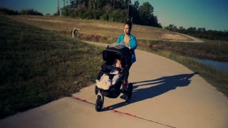 tracking shot mother exercising with baby in stroller 4k