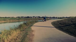 tracking shot of mother jogging with baby stroller past camera 4k