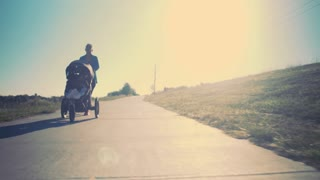 tracking shot of mother jogging with baby stroller sun flare 4k