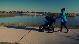 tracking shot of mother jogging with her baby in the stroller 4k