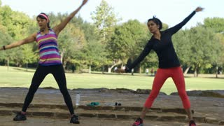 twin sisters doing side stretching before exercise in a park