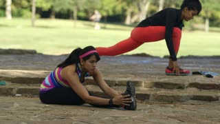 twin sisters stretching and doing situps in a park