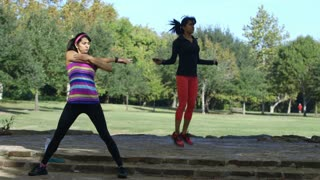 twin sisters stretching and exercising in a park