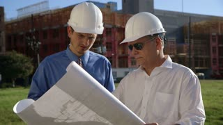 two construction engineers going over building plans
