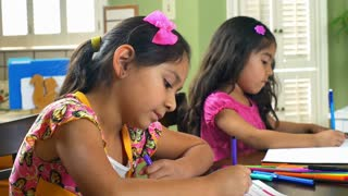 two cute little girls doing homework smile at camera 4k.