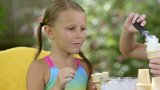 two cute little girls eating ice cream