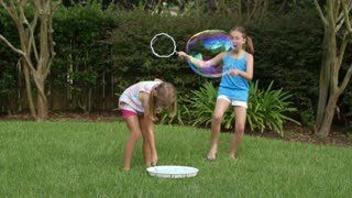 two cute little girls playing with bubbles outside