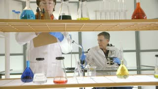 Two lab techs working on a solution.