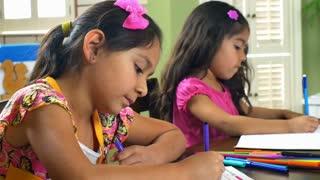 two little girls doing homework smile at camera.