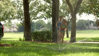 two little girls jump over sprinkler and run towards camera