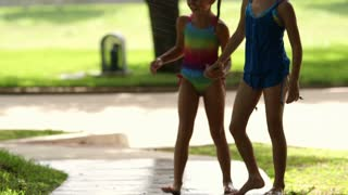 two little girls running and jumping over the sprinkler