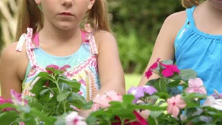 two little girls smelling flowers