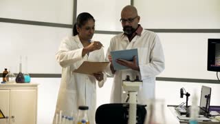 two scientists standing and going over notes in their lab 4k