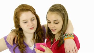 two teenage girls listening to music isolated over white.