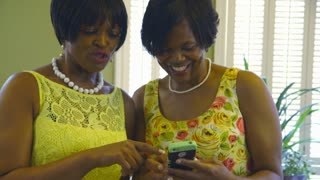 two women laughing at something on the cell phone.