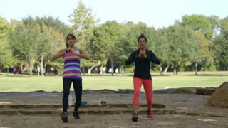 two women warming up with lunges before exercising in a park