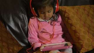 two young Indian girls on sofa each watching own tablet pc