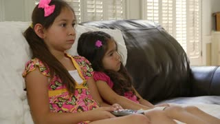 two young sisters watching TV