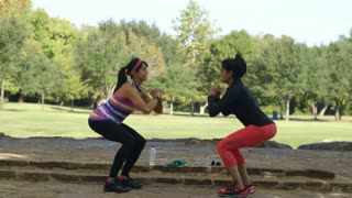 two young women doing squats and stretching in a park