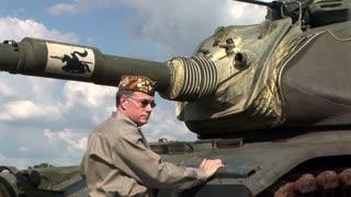 vfw veteran next to an army tank