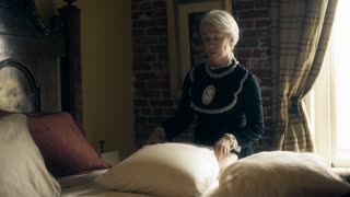 Victorian era woman making the bed in her home 4k