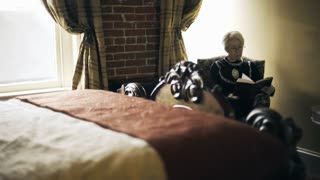 Victorian era woman reading a book or bible in her bedroom 4k