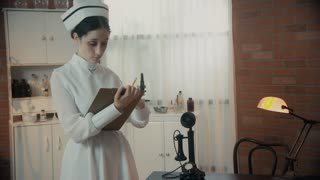 1930 S Nurse Standing Writing On A Clipboard In The Doctors Office Color Version