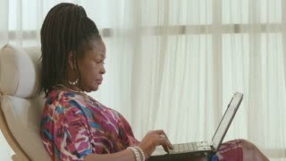 African American woman shopping online smiles at camera