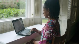 African American Woman with Laptop Shopping for Shoes Online