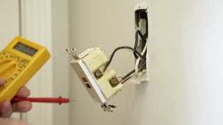 an electrician checking voltage on a ground fault outlet 4k