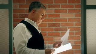 Businessman In Office Doorway Looking At Paperwork