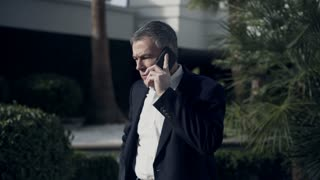 businessman outside a luxury hotel talking on his cellphone 4k